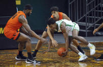 Oregon State forward Rodrigue Andela, left, and Julien Franklin defend against Oregon forward Eric Williams Jr. during the first half of an NCAA college basketball game Saturday, Jan. 23, 2021, in Eugene, Ore. (AP Photo/Andy Nelson)