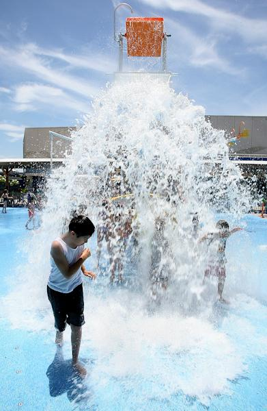 Ernest Rivera, 10, runs from the gallons of water pouring down on him and other children trying to beat the heat Friday, June 28, 2013 at the Texas State Aquarium's HEB Splash Park in Corpus Christi, Texas. (AP Photo/Corpus Christi Caller-Times, Todd Yates) MANDATORY CREDIT; MAGS OUT; TV OUT
