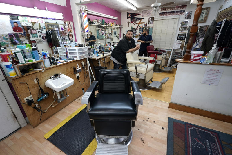 FILE - In this March 20, 2020 file photo, Carlos Vasquez, left, and his nephew R.J. Vasquez, wait for customers at their family's barber shop in Houston.  Reaction to the coronavirus, change came to the United States during the third week of March in 2020. It did not come immediately, though it came quite quickly. There was no explosion, no invasion other than a microscopic one that nobody could see.   (AP Photo/David J. Phillip, File)