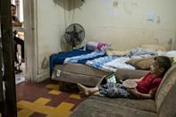 Gerald Josseph Trujillo Martinez watches a video on his tablet while his mother Ana Gabriela Martinez teaches a class at their home in Matamoros, Mexico on May 25, 2021