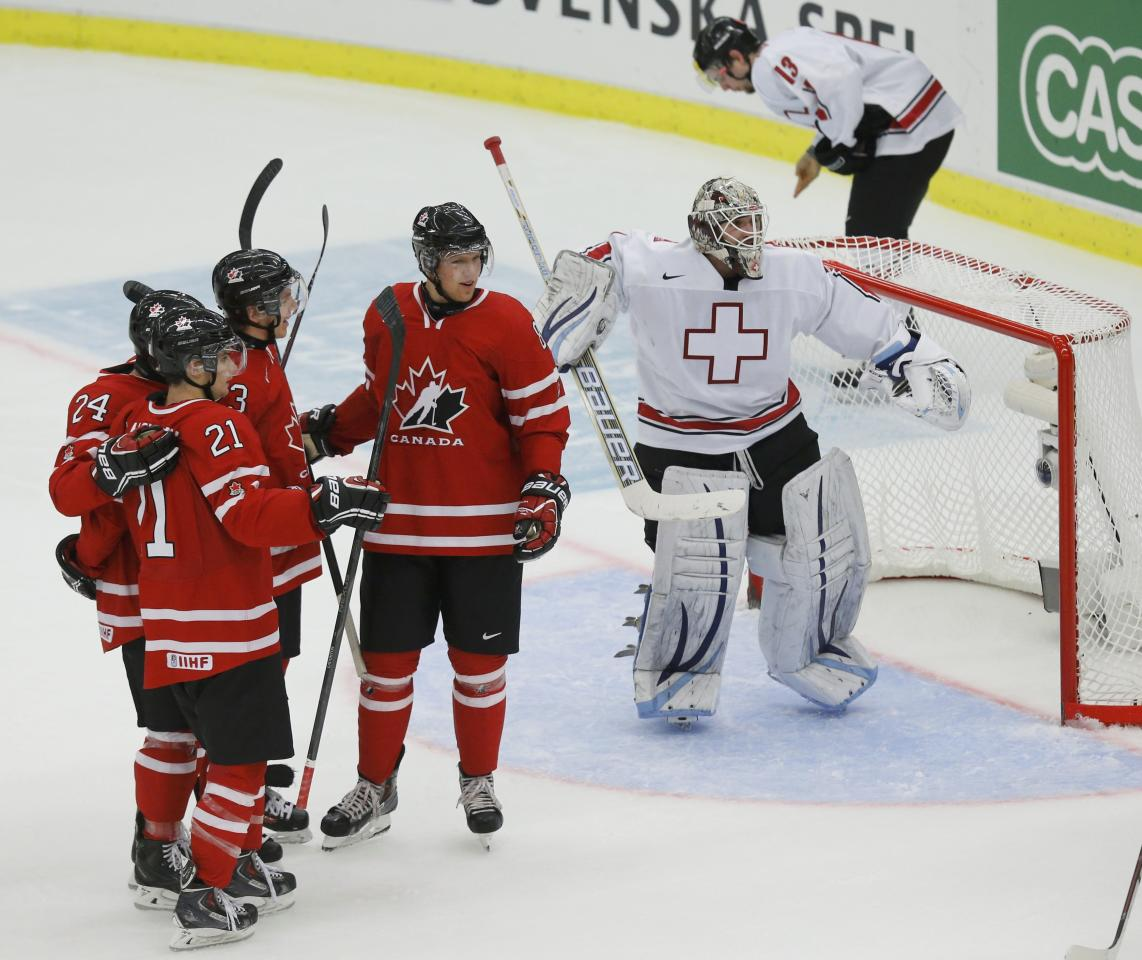 Canada's Griffin Reinhart (C), celebrates his goal on Switzerland's goalie Melvin Nyffeler (R) with teammates Mathew Dumba (24), Scott Laughton (21), and Sam Reinhart during the first period of their IIHF World Junior Championship ice hockey game in Malmo, Sweden, January 2, 2014. REUTERS/Alexander Demianchuk (SWEDEN - Tags: SPORT ICE HOCKEY)