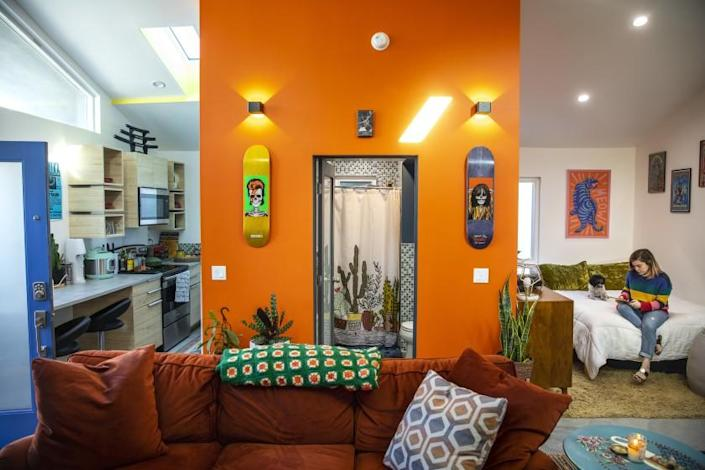 LOS ANGELES, CA - FEBRUARY 19: Color fills the rental of John Velasco and Ariel Gomez-Hernandez, which is an accessory dwelling unit, built by architect Alexis Navarro, on a property he own in Los Angeles, CA, Friday, Feb. 19, 2021. Gomez-Hernandez added two skateboards from her collection, as contrasts against the orange wall painted by Navarro. Navarro built the studio ADU where a car port was stood, between a duplex and another single unit, on the property. (Jay L. Clendenin / Los Angeles Times)