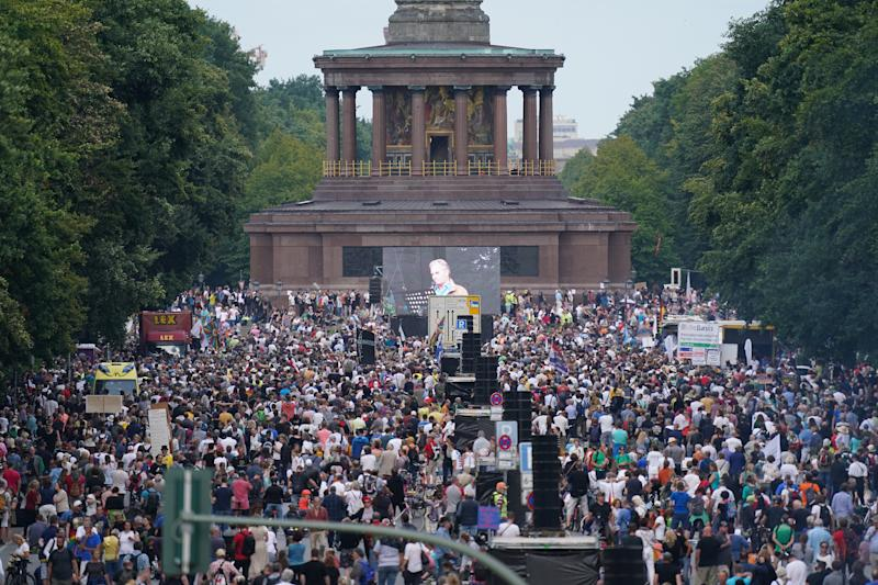 BERLIN, GERMANY - AUGUST 29: People gather at the Victory Column in the city center to hear speeches during a protest against coronavirus-related restrictions and government policy on August 29, 2020 in Berlin, Germany. Tens of thousands of people from a wide spectrum, including coronavirus skeptics, conspiracy enthusiasts, hippies, right-wing extremists, religious conservatives and others converged on Berlin to attend the protests. City authorities had banned the protests, citing the flouting of social distancing by participants in a similar march that drew at least 17,000 people a few weeks ago, but a court overturned the ban. (Photo by Sean Gallup/Getty Images)