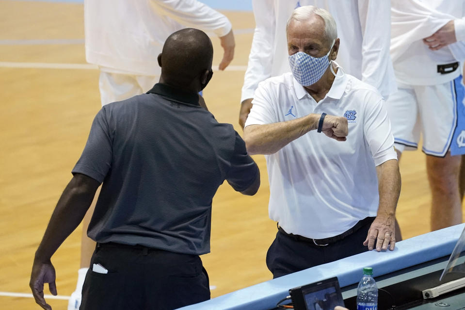 North Carolina coach Roy Williams, right, greets College of Charleston coach Earl Grant prior to an NCAA college basketball game in Chapel Hill, N.C., Wednesday, Nov. 25, 2020. (AP Photo/Gerry Broome)
