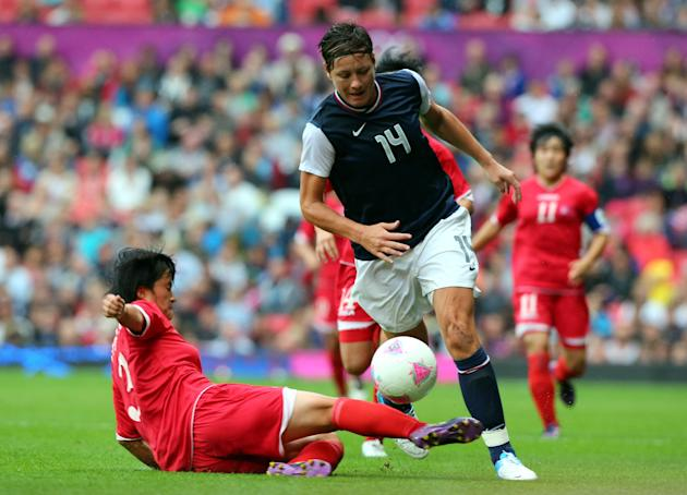 Abby Wambach of United States is tackled by Kim Myong Gum of DPR Korea during the Women's Football first round Group G match between the United States and DPR Korea,on Day 4 of the London 2012 Olympic Games at Old Trafford on July 31, 2012 in Manchester, England. (Stanley Chou/Getty Images)