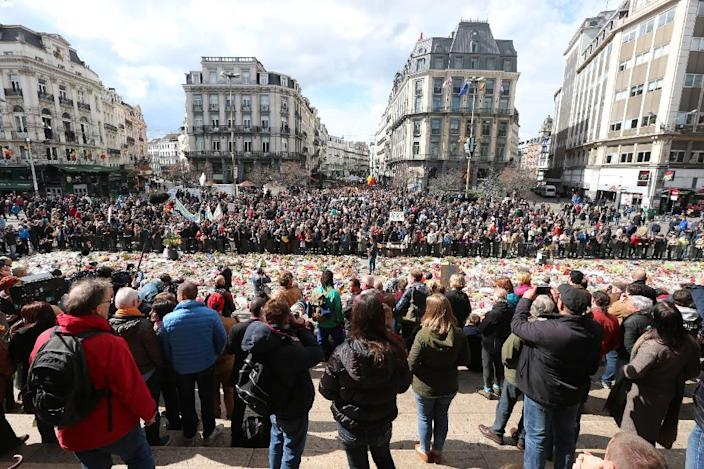 """People stand by the makeshift memorial outside the Stock Exchange in Brussels during the """"#Tousensemble - #Sameneen"""" march against jihadist violence on April 17, 2016 (AFP Photo/Nicolas Maeterlink)"""