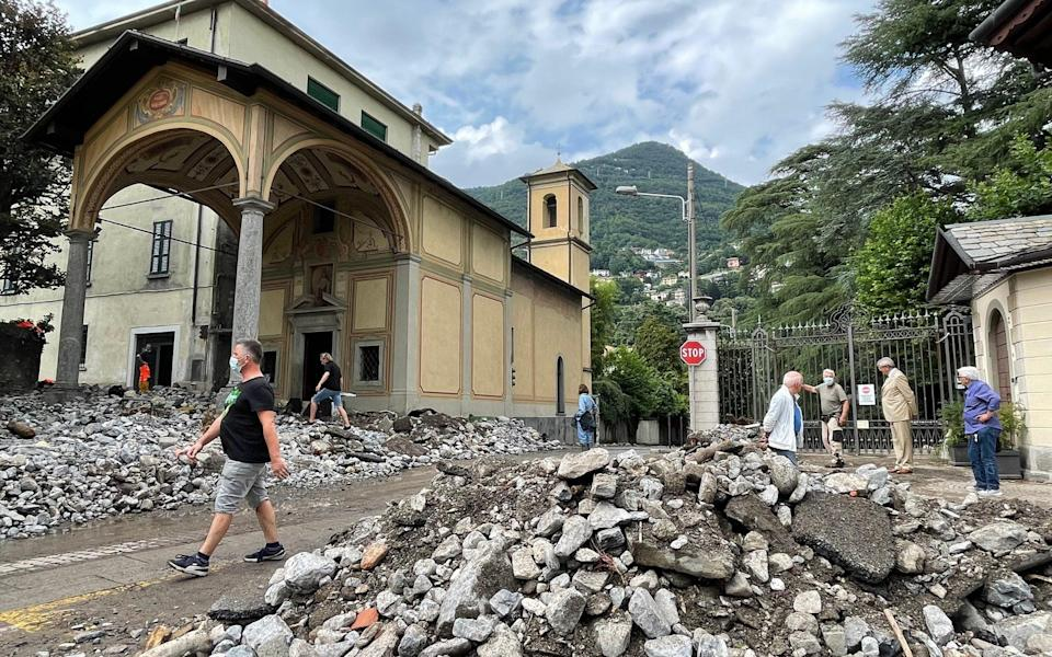Passers-by stand next to the debris that a storm has washed up in Cernobbio, northern Italy - Bernhard Krieger/Avalon