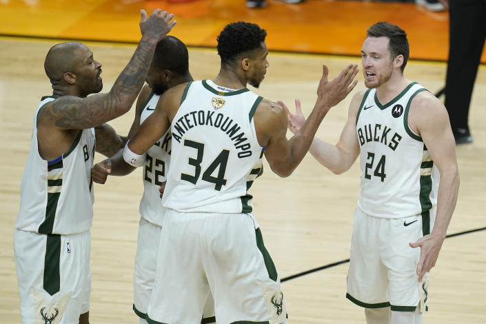 Milwaukee Bucks' P.J. Tucker, from left, celebrates with Khris Middleton, Giannis Antetokounmpo and Pat Connaughton during the second half of Game 5 of basketball's NBA Finals against the Phoenix Suns, Saturday, July 17, 2021, in Phoenix. (AP Photo/Ross D. Franklin)