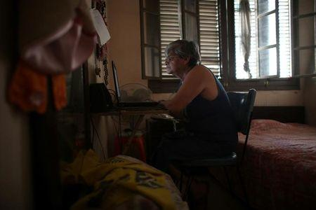 Retired teacher Margarita Marquez, 67, uses the Internet after it was recently installed at her home in old Havana, Cuba