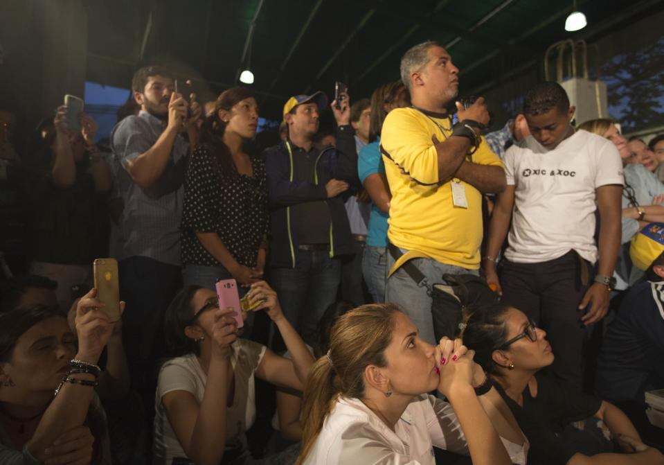 Journalist and supporters listen to Venezuelan opposition leader Henrique Capriles, not seen, during a meeting in Caracas, Venezuela, Friday, April, 7, 2017. Capriles announced that he has been banned from running for office for 15 years, a move sure to ratchet up tensions amid a growing street protest movement. (AP Photo/Ariana Cubillos)