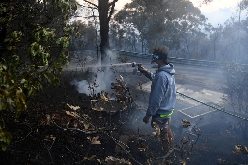 A resident hoses smouldering logs as a bushfire burns in Woodford NSW