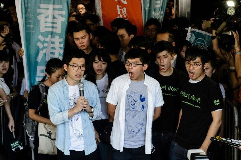 Joshua Wong (C), with fellow activists Nathan Law (L) and Alex Chow (R), was jailed in August over the protest that sparked the Umbrella Movement demonstrations in 2014