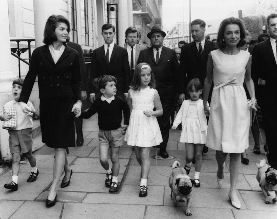 <p>Jackie and her sister Princess Lee Radziwill take their children and dogs for a walk, surrounded by security, in London. </p>