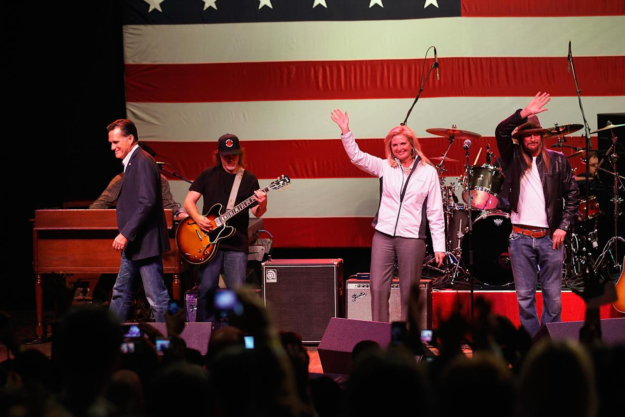 ROYAL OAK, MI - FEBRUARY 27:  Republican presidential candidate, former Massachusetts Gov. Mitt Romney (L) walks away as Ann Romney and musician Kid Rock wave during a campaign event at the Royal Oak Music Theatre on February 27, 2012 in Royal Oak, Michigan. Michigan residents will go to the polls on February 28 to vote for their choice in the Republican presidential race.  (Photo by Joe Raedle/Getty Images)