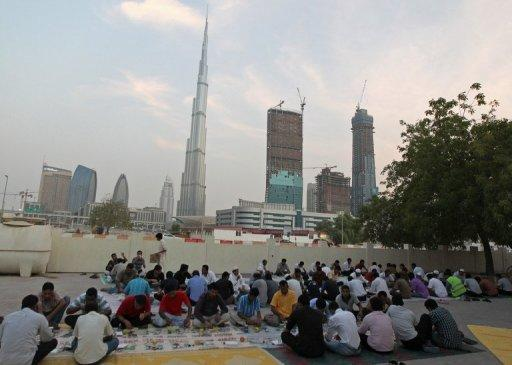 """Muslims break their fast during Ramadan last year outside a mosque near the Burj Khalifa tower in Dubai. The Gulf emirate's proposed """"Mall of the World"""" will have a capacity of 80 mn visitors a year to become the """"largest in the world,"""" said the statement, while its park will be """"30% bigger than Hyde Park of London."""""""