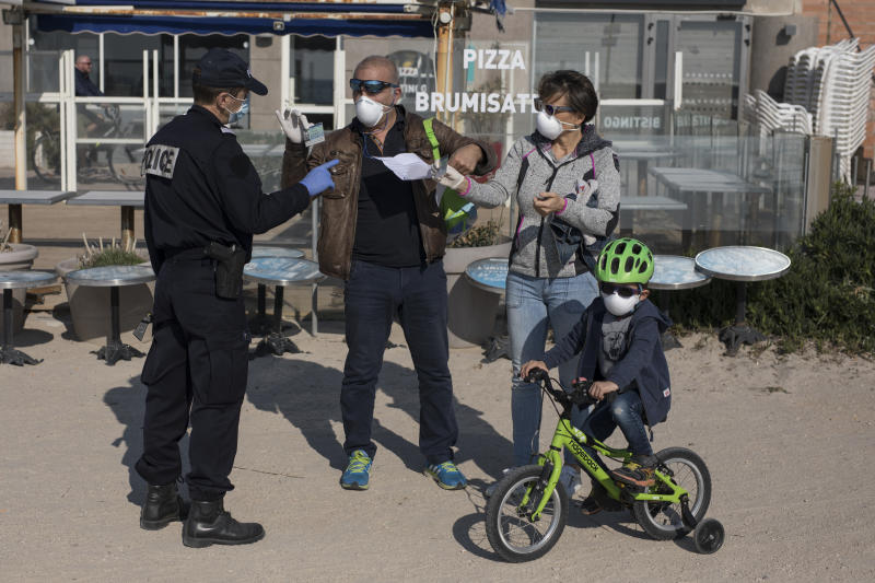 A French police officer checks the documents of a family on a beach in Marseille, southern France, Thursday, March 19, 2020. French President Emmanuel Macron said that for 15 days people will be allowed to leave the place they live only for necessary activities such as shopping for food, going to work or taking a walk. For most people, the new coronavirus causes only mild or moderate symptoms. For some it can cause more severe illness, especially in older adults and people with existing health problems. (AP Photo/Daniel Cole)