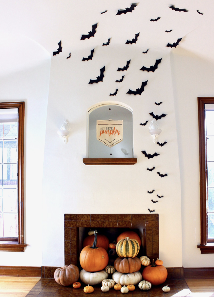 brown stone fireplace with white wall and windows, pumpkins at fireplace and paper bats on wall