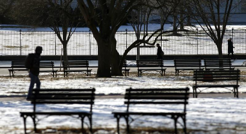 Pedestrians make their way past vacant benches in snowy Lafayette Park in front of the White House in Washington