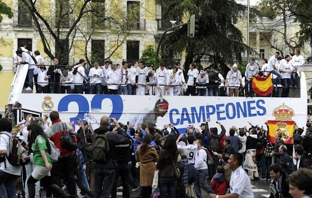 Real Madrid's players celebrate on an open bus surrounded by supporters at Cibeles square in Madrid on May 3, 2012, a day after winning the Spanish league title for the first time since 2008. Real Madrid's 3-0 away win over Athletic Bilbao sealed the league, putting them seven points clear of last year's winners and arch rivals Barcelona with just two games to go and delivering the team's 32nd league crown. AFP PHOTO / DOMINIQUE FAGETDOMINIQUE FAGET/AFP/GettyImages