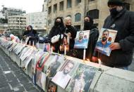 Relatives of victims of Beirut port explosion, hold their pictures during a protest demanding justice, at the entrance of Beirut port