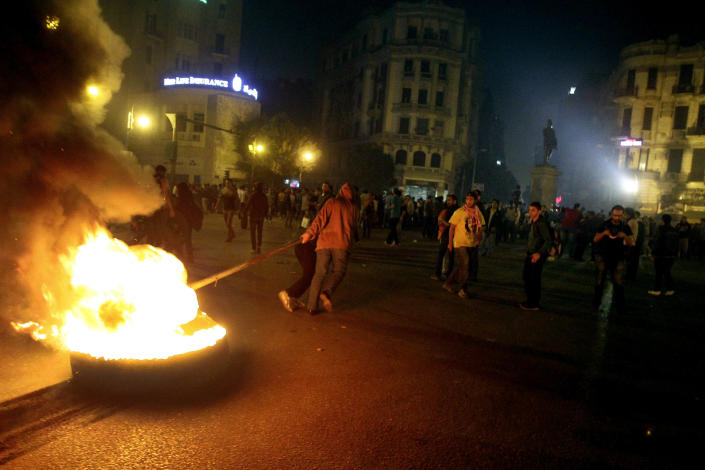 In this Tuesday, Nov. 26, 2013 photo, secular Egyptian activists drag a burning tire towards Talaat Harb Square, during a protest in Downtown, Cairo, Egypt. Egypt's state news agency says the prosecutor general has ordered a four-day detention for 24 activists detained while protesting a newly passed law criminalizing demonstrations without permits. MEAN also says the prosecutor on Wednesday issued arrest warrants for two leading activists accused of inciting demonstrators. (AP Photo/El-Shorouk Newspaper, Ahmed Abd el-Latif) EGYPT OUT