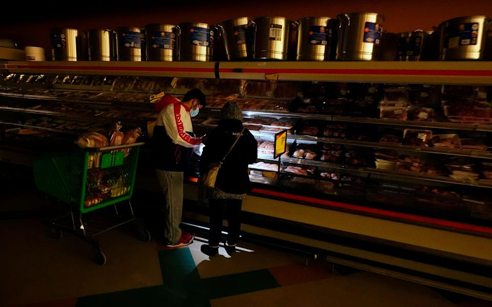 Customers use the light from a cellphone to look in the meat section of a Dallas grocery store on Feb. 16. Though the store lost power, it was open for cash-only sales. (Photo: LM Otero/AP)