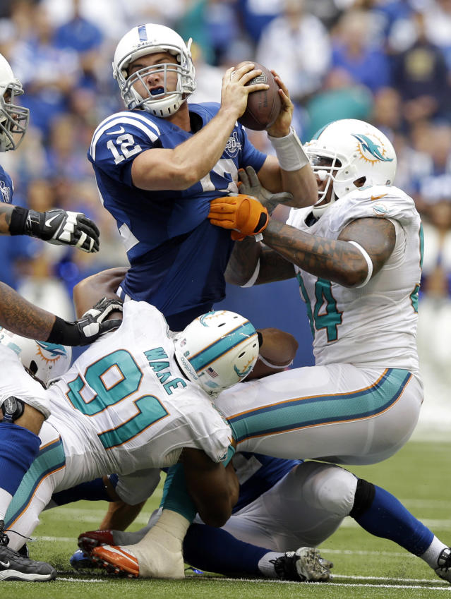 Indianapolis Colts' Andrew Luck (12) tries to throw the football as he is sacked by Miami Dolphins' Philip Wheeler (52), behind, during the second half an NFL football game Sunday, Sept. 15, 2013, in Indianapolis. (AP Photo/Michael Conroy)