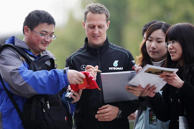 SHANGHAI, CHINA - APRIL 13: Michael Schumacher of Germany and Mercedes GP signs autographs following practice for the Chinese Formula One Grand Prix at the Shanghai International Circuit on April 13, 2012 in Shanghai, China. (Photo by Mark Thompson/Getty Images)