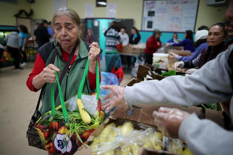 A woman collects provisions at a food bank for the poor in Los Angeles: Reuters