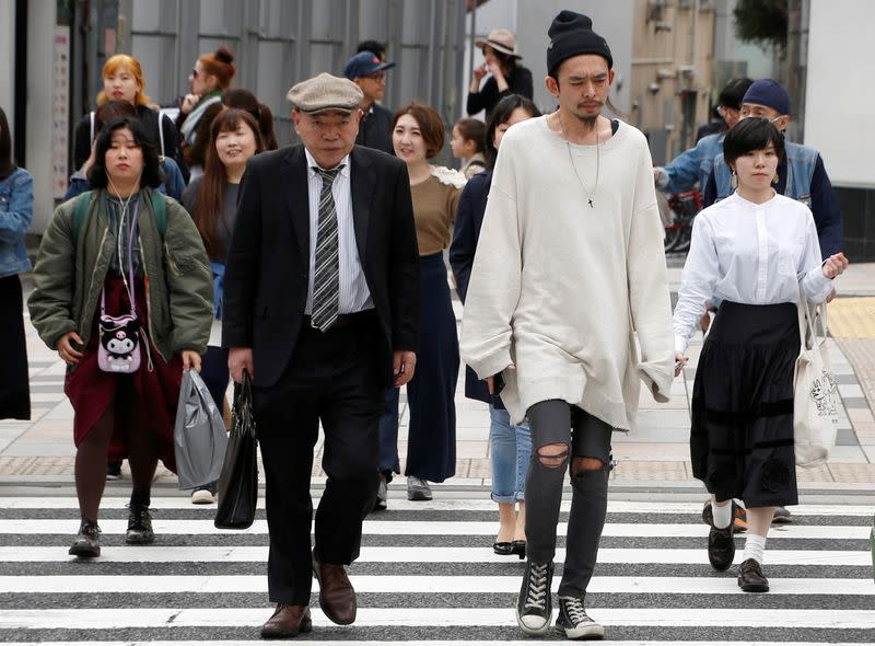FILE PHOTO: Pedestrians cross the street at a crosswalk at Omotesando shopping district in Tokyo