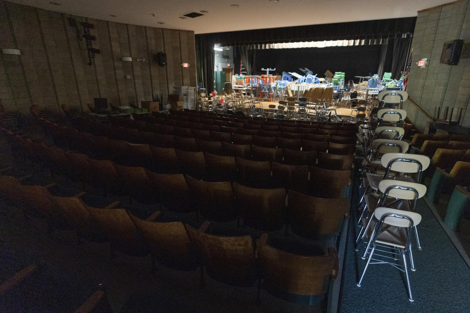 Desks and supplies sit stacked in the auditorium which is being used as storage during the coronavirus outbreak at the Osborn School, Tuesday, Oct. 6, 2020, in Rye, N.Y. (AP Photo/Mary Altaffer)