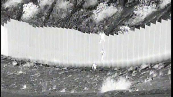 PHOTO: This photo taken from night video and provided by the United States Customs and Border Protection shows a smuggler dropping children from the top of a border barrier near Santa Teresa, New Mexico, on March 30, 2021. (U.S. Customs and Border Protection via AP)