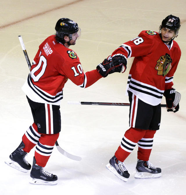 Chicago Blackhawks' Patrick Sharp (10), left, celebrates with teammate Patrick Kane (88) after scoring a goal during the third period in Game 6 of a first-round NHL hockey playoff series against St. Louis Blues in Chicago, Sunday, April 27, 2014. The Blackhawks won 5-1. (AP Photo/Nam Y. Huh)