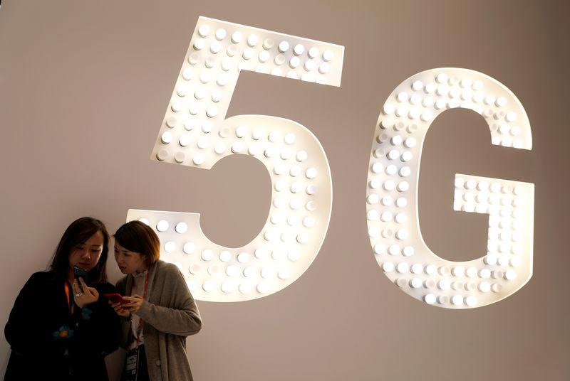 Visitors use their mobiles phones as they stand next to a 5G Led Smart Bulb panel inside the Xiaomi booth at the Mobile World Congress in Barcelona