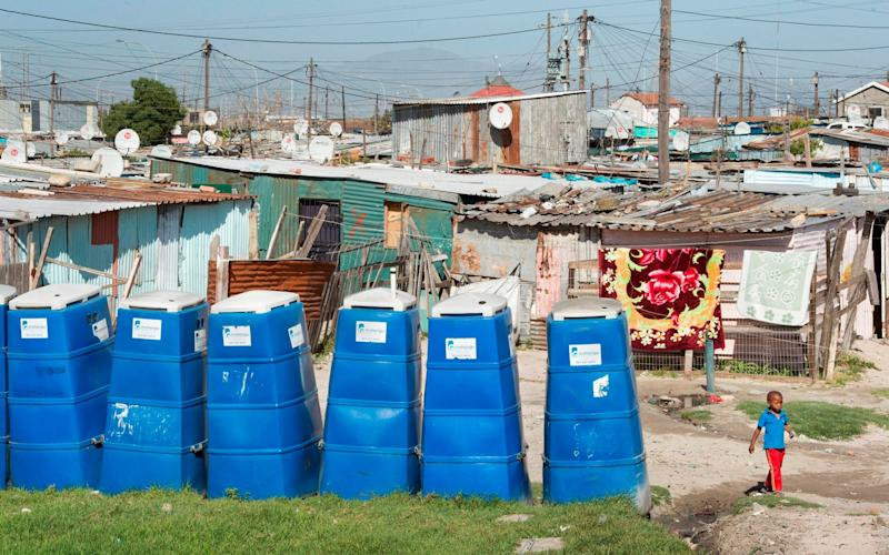 A row of portable toilets at an informal settlement in Khayelitsha, Cape Town - AFP