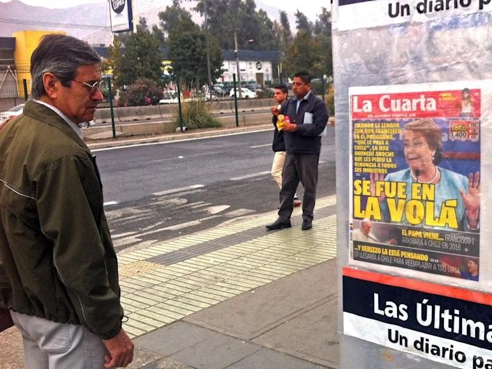 A man reads a newspaper cover announcing a surprise cabinet reshuffle, showing a portrait of Chilean President Michelle Bachelet, in Santiago on May 7, 2015 (AFP Photo/Martin Bernetti)