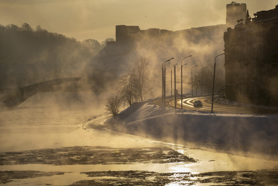 A car makes its way through a street along the snow covered banks of the Neris river during the sun rises as temperatures dipped to -21 degrees Celsius (-5.8 degrees Fahrenheit) in Vilnius, Sunday, Feb. 7, 2021. (AP Photo/Mindaugas Kulbis)