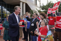 Virginia Republican gubernatorial candidate Glenn Youngkin and his wife Suzanne greet supporters after voting early, Thursday, Sept. 23, 2021, in Fairfax, Va. (AP Photo/Patrick Semansky)