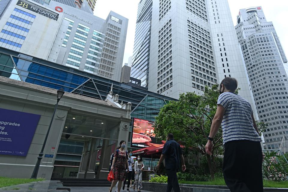 People walk along promenade during lunch break at Raffles Place financial business district in Singapore on June 15, 2020. - A polled survey from economists and analysts conducted by the Monetary Authority of Singapore (MAS) and released on June 15, indicates Singapore economy is expected to contract by 5.8 per cent this year. (Photo by Roslan RAHMAN / AFP) (Photo by ROSLAN RAHMAN/AFP via Getty Images)