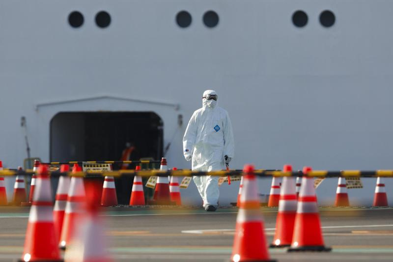 A health worker in a protective suit walks near the quarantined Diamond Princess cruise ship on Wednesday: AP