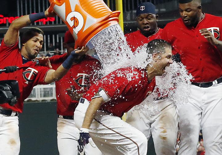 Joe Mauer is doused by his Twins teammates after hitting his first career walk-off solo home run in a win against the Red Sox. (AP)