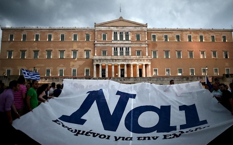 """Pro-euro protesters hold a banner reading ''YES"""" during a demonstration in front of the parliament in Athens on June 30, 2015 (AFP Photo/Aris Messinis)"""