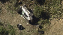 """In this aerial image take from video provided by KABC-TV, a vehicle rest on its side after a rollover accident involving golfer Tiger Woods along a road in the Rancho Palos Verdes suburb of Los Angeles on Tuesday, Feb. 23, 2021. Woods had to be extricated from the vehicle with the """"jaws of life"""" tools, the Los Angeles County Sheriff's Department said in a statement. Woods was taken to the hospital with unspecified injuries. The vehicle sustained major damage, the sheriff's department said. (KABC-TV via AP)"""