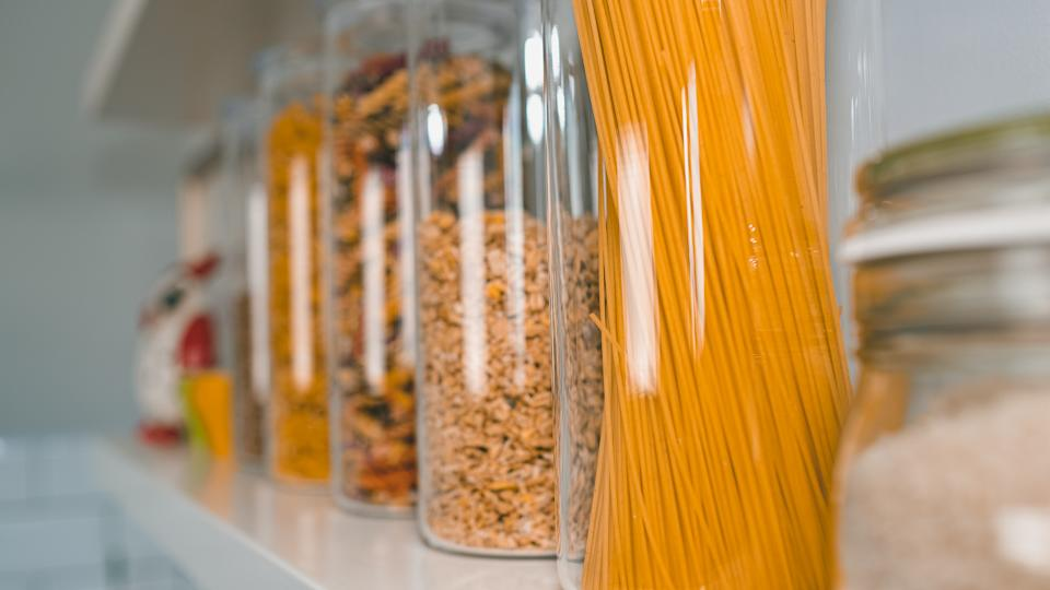 Various uncooked groceries in glass jars arranged on wooden white shelves ar the kitchen.