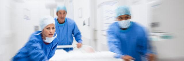 Nurse and doctor in a hurry taking patient to operation theatre. Patient on hospital bed pushed from surgeon to emergency theatre. Team of doctors and surgeon rushing patient. (Nurse and doctor in a hurry taking patient to operation theatre. Patient o
