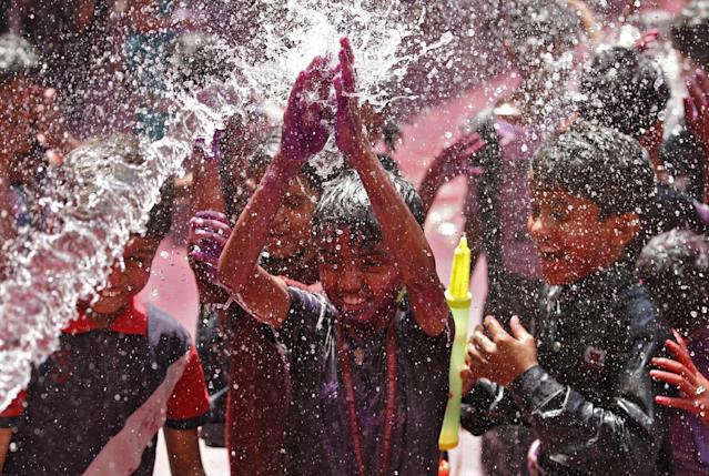 Students cheer as water is sprayed on them during Holi celebrations at a school in the western Indian city of Ahmedabad March 14, 2014. Holi, also known as the Festival of Colours, heralds the beginning of spring and is celebrated all over India. REUTERS/Amit Dave (INDIA - Tags: RELIGION SOCIETY)
