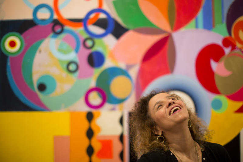 """Brazilian artist Beatriz Milhazes poses for a photo in front of one of her paintings in Rio de Janeiro, Brazil, Friday, Aug. 23, 2013. """"I've shown in places that are obviously very exciting for any artist, but in a way showing in your city _ I was born here and still live and work here _ kind of grabs you more, excites you more, stirs you up more,"""" Milhazes told The Associated Press in a Friday interview as she supervised the installation of the exhibit, entitled """"Meu Bem,"""" Portuguese for """"My Dear."""" """"It's being able to say, 'Mom, look what I've done.'"""" (AP Photo/Felipe Dana)"""