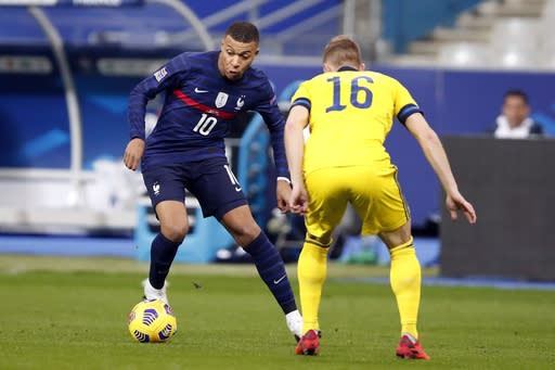 France's Kylian Mbappe, left, controls the ball as Sweden's Emil Krafth defends during the UEFA Nations League soccer match between France and Sweden at the Stade de France stadium in Saint-Denis, northern Paris, Tuesday, Nov. 17, 2020. (AP Photo/Francois Mori)