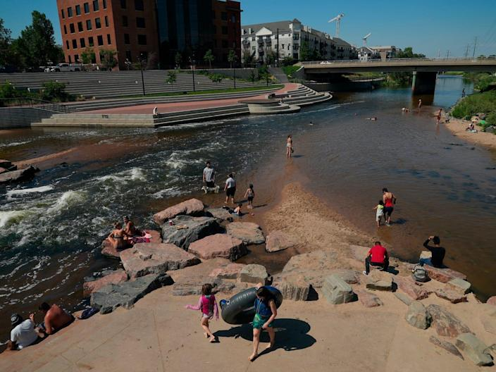 People in the water the confluence of the South Platte River and Cherry Creek in Denver.
