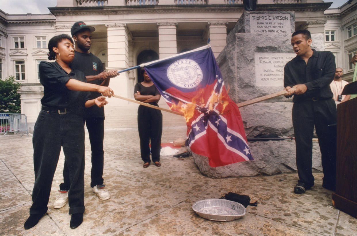 "Burning Georgia's ""racist past"" is how Lawrence Jeffries, right, described the flag-burning at the Capitol in June 1992. The flag then included the Confederate symbol. From left are Ina Solomon, Jeffery Harris and Stacey Abrams. (Photo: W.A. Bridges Jr./Atlanta Journal-Constitution)"